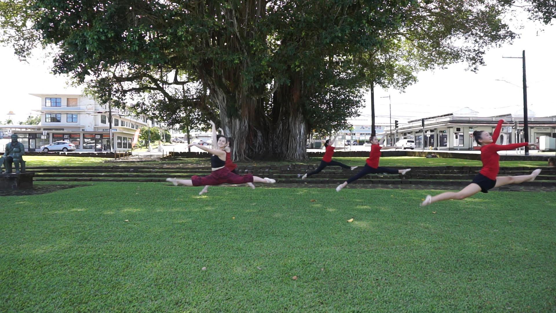 Dancers leap in unison at Kalakaua Park, Hilo.