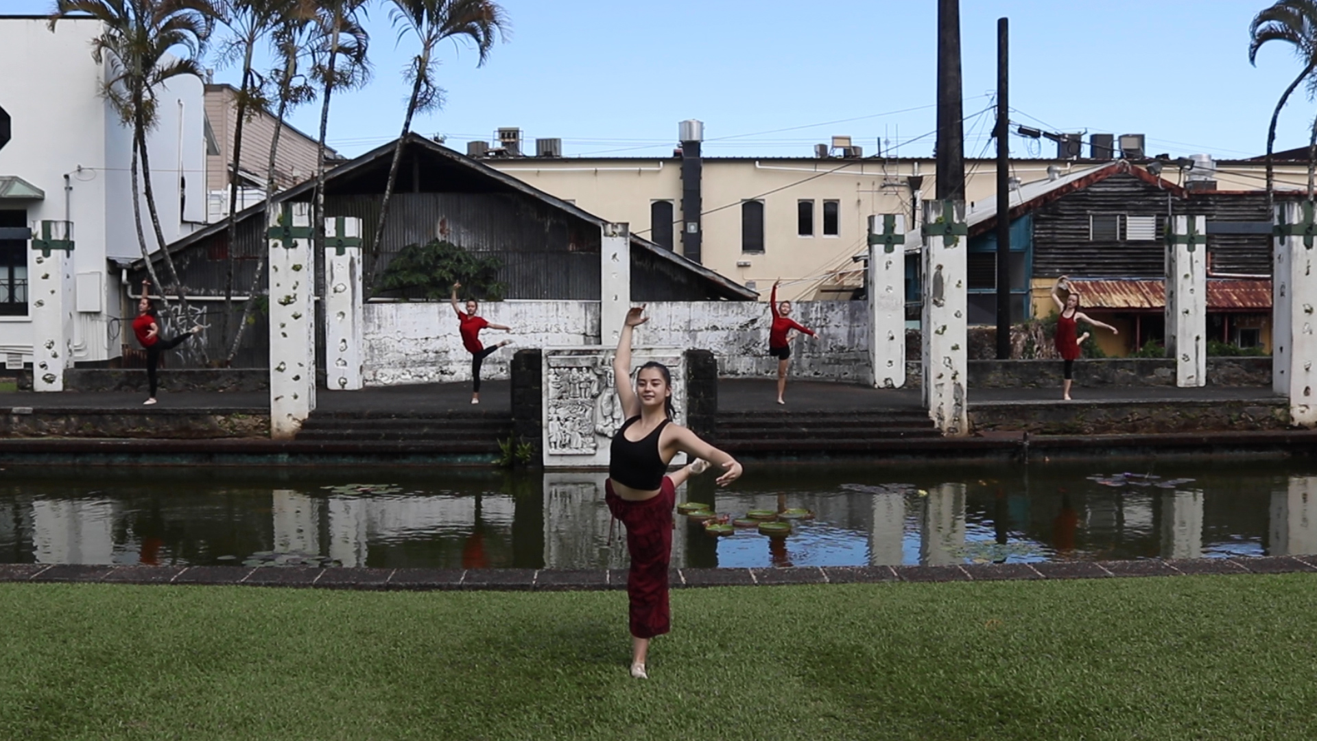 Group of ballet dancers wearing black and red near water feature at Kalakaua Park.
