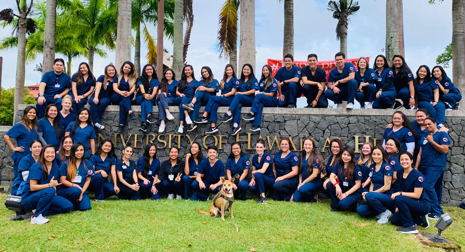 A group photo of the School of Nursing cohort, taken on the lava wall at the main entrance of UH Hilo. The students wear dark blue scrubs.