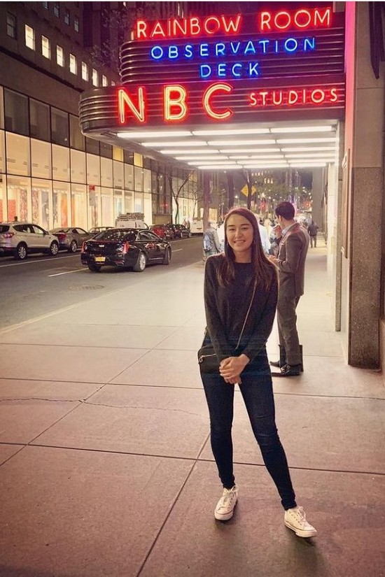 Alexandria stands next to brightly lit marquee in NYC street.