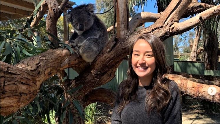 Alexandria stands next to a koala bear in a tree.