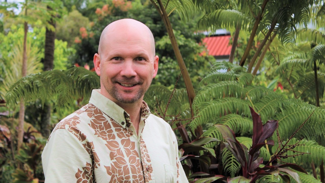 Chris Holland in aloha shirt with gardens in background.