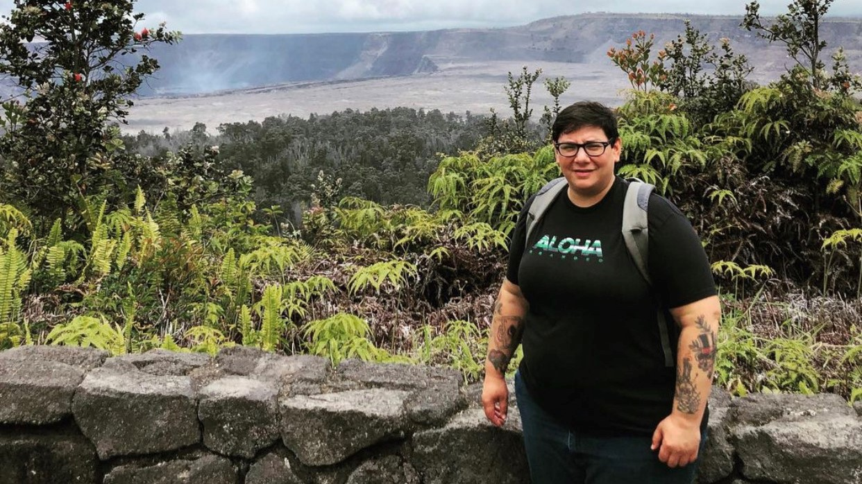 Heather, with backpack, stands for photo, Halema'uma'u crater and ohia trees in the background.