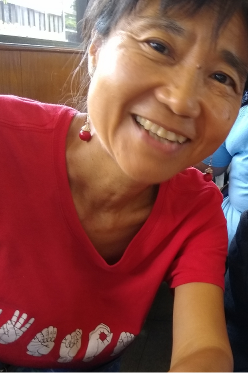 Yoshiko is pictured in a red t-shirt with sign language on the front.