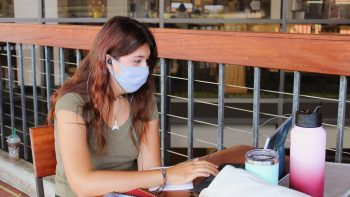 Young woman in mask studying on laptop, Library Lanai.