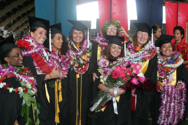Group of graduates in cap and gown. All wear lei. Christine Park holds bouquet of roses.