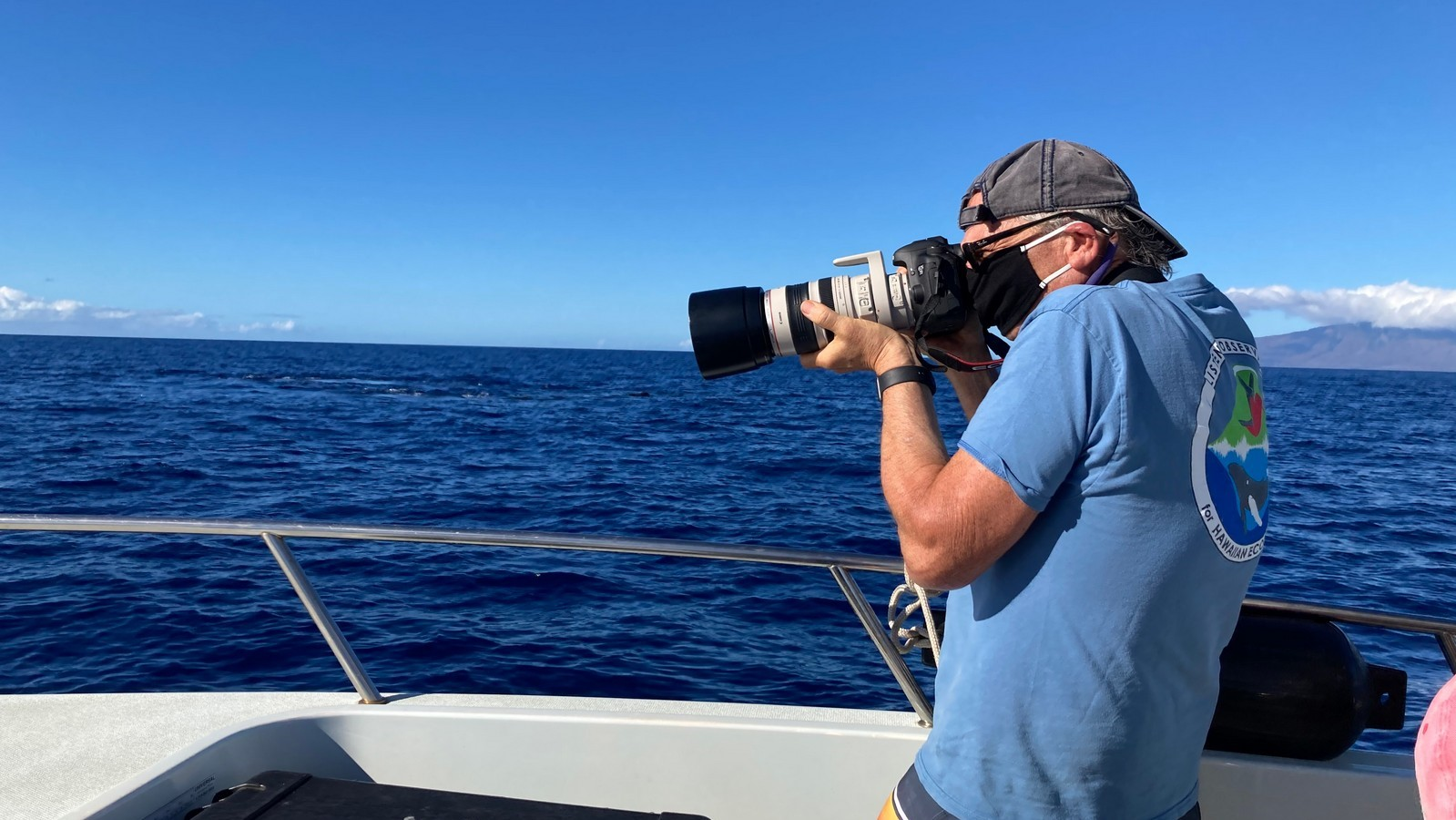 Adam Pack on boat at sea, holding and looking through telephoto lens.