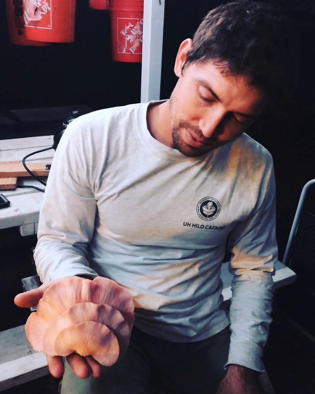 Jake holds a huge pink mushroom.