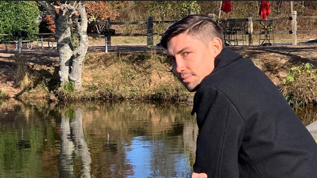 Jake stands near a waterway.