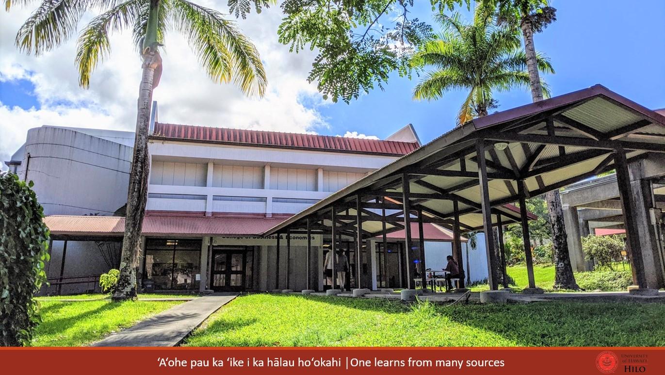 Two-story building with covered walkway, red roof. At bottom of slide: ʻAʻohe pau ka ʻike i ka hālau hoʻokahi/One learns from many sources.