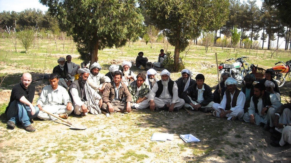 Hourihan sits on ground with group of Afghan men seated in a semicircle in an orchard.