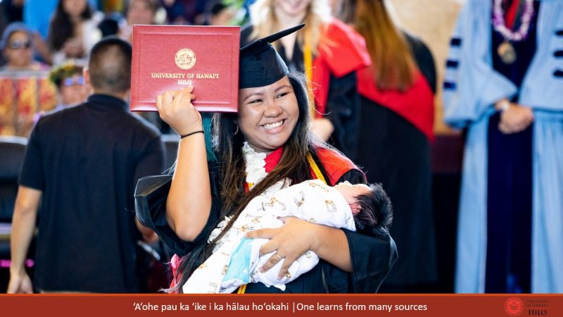 Graduate holding diploma cover in one hand, and cradling baby in the other. At bottom of slide: ʻAʻohe pau ka ʻike i ka hālau hoʻokahi/One learns from many sources.