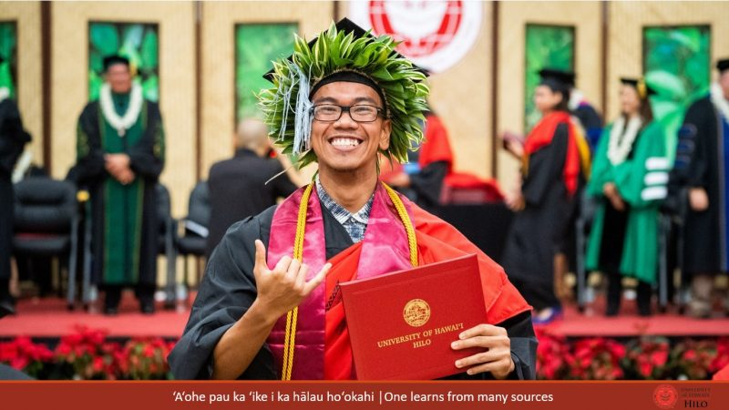 Male with head lei, holding diploma and giving the shaka. At bottom of slide: ʻAʻohe pau ka ʻike i ka hālau hoʻokahi/One learns from many sources.