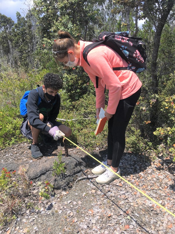 One student crouches down and another stands as they measure crack in ground.