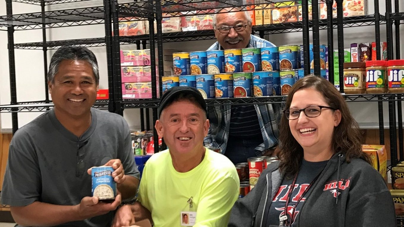 Four staff members pose for photo while stocking shelves in pantry.
