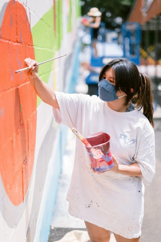 Lillian Lewis paints mural.