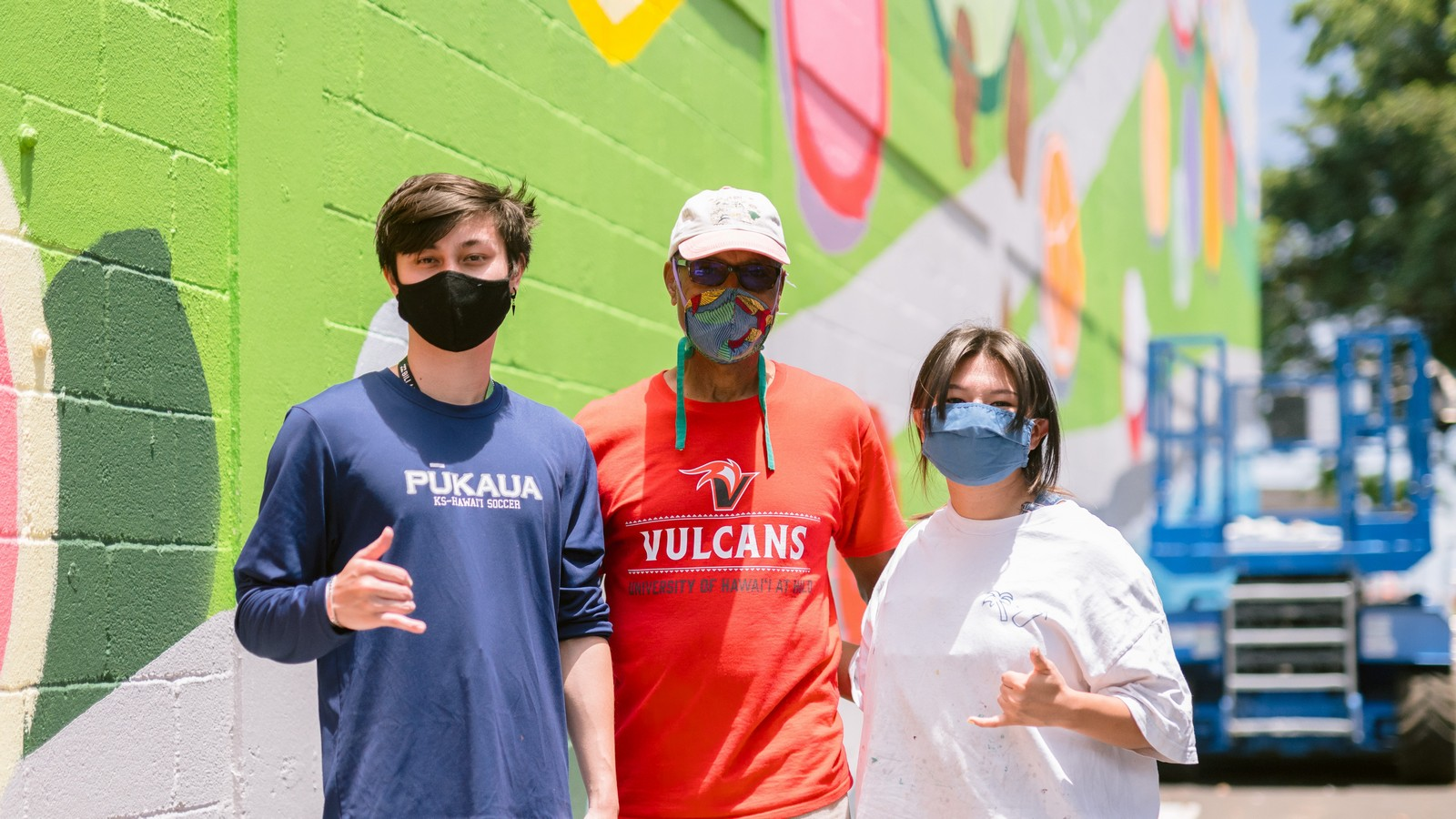 Three people stand for photo in front of colorful mural.