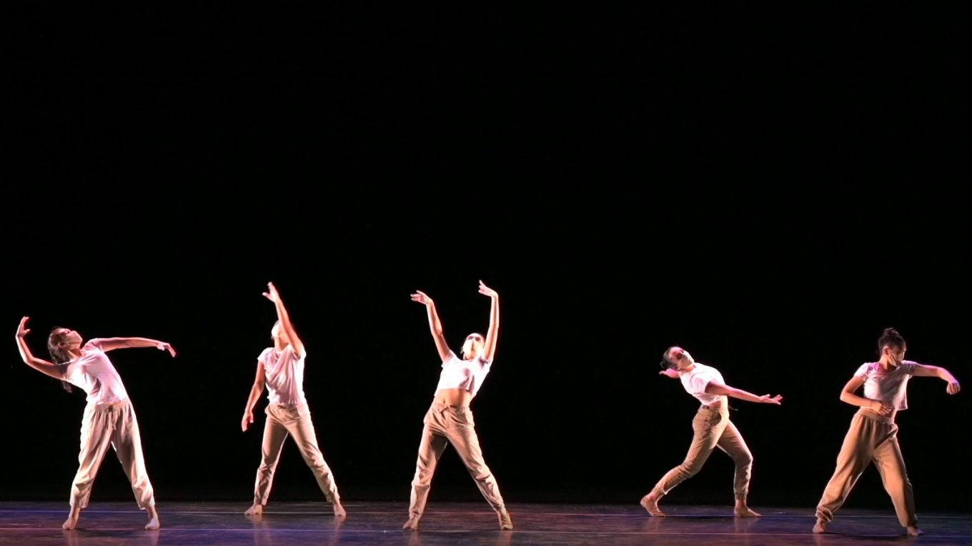 Five dancers in various poses on a large stage.