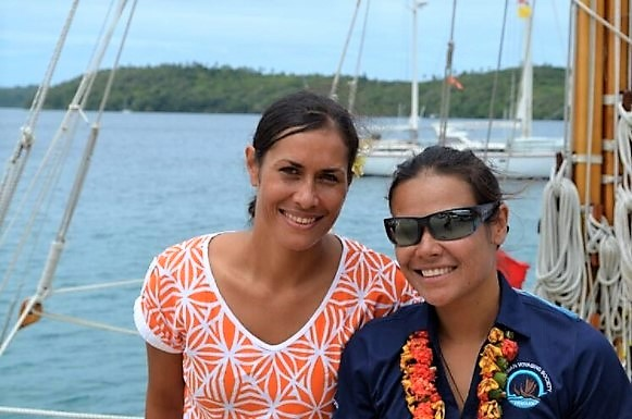 Two women pose for photo on voyaging canoe.