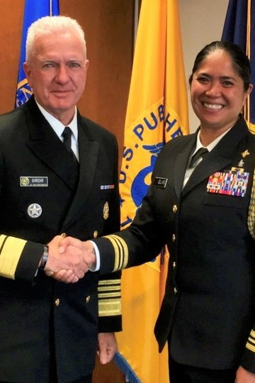 Two people in uniform shake hands.
