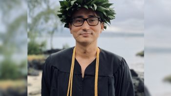 Nicholas Iwamoto in graduation robes