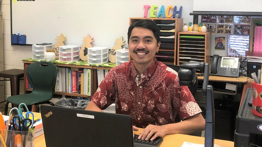 Jay Bamanglag at his desk in his classroom.