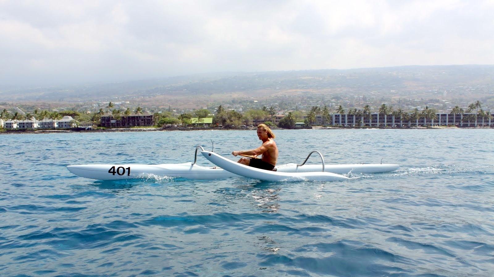 Prof. Barkhoff paddling in a one-man canoe in Keauhou Bay. Island in background.