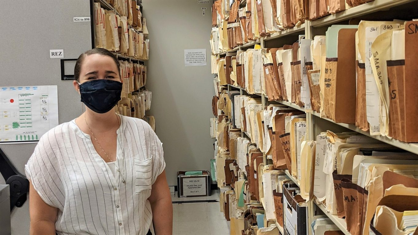 Shawna stands in a room with shelves and shelves of traditional file folders.