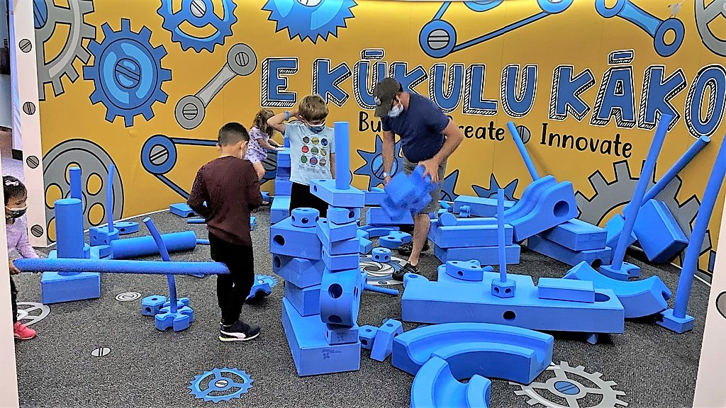 Keiki and adult working in large interactive exhibit of large gears.