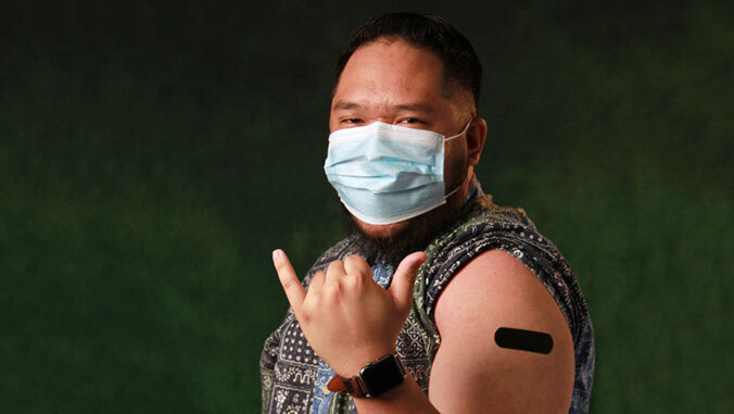Man with bandaid on arm from vaccination. Shaka!