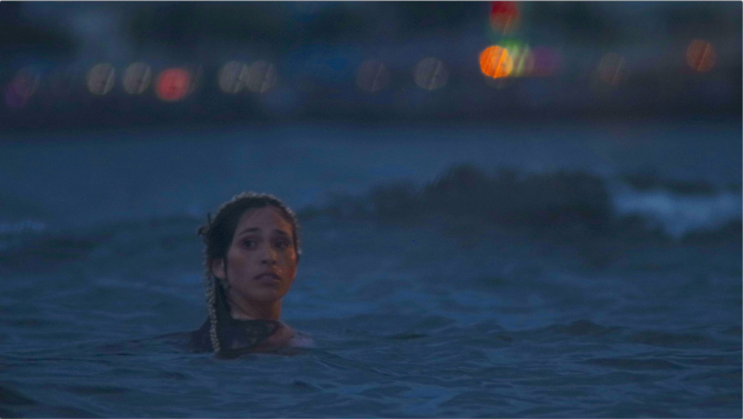 Woman with head just above ocean water, looks back with worried expression.