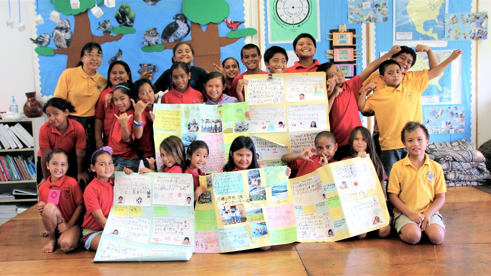 Photo of class, some students holding up large posters of Japanese language lessons.