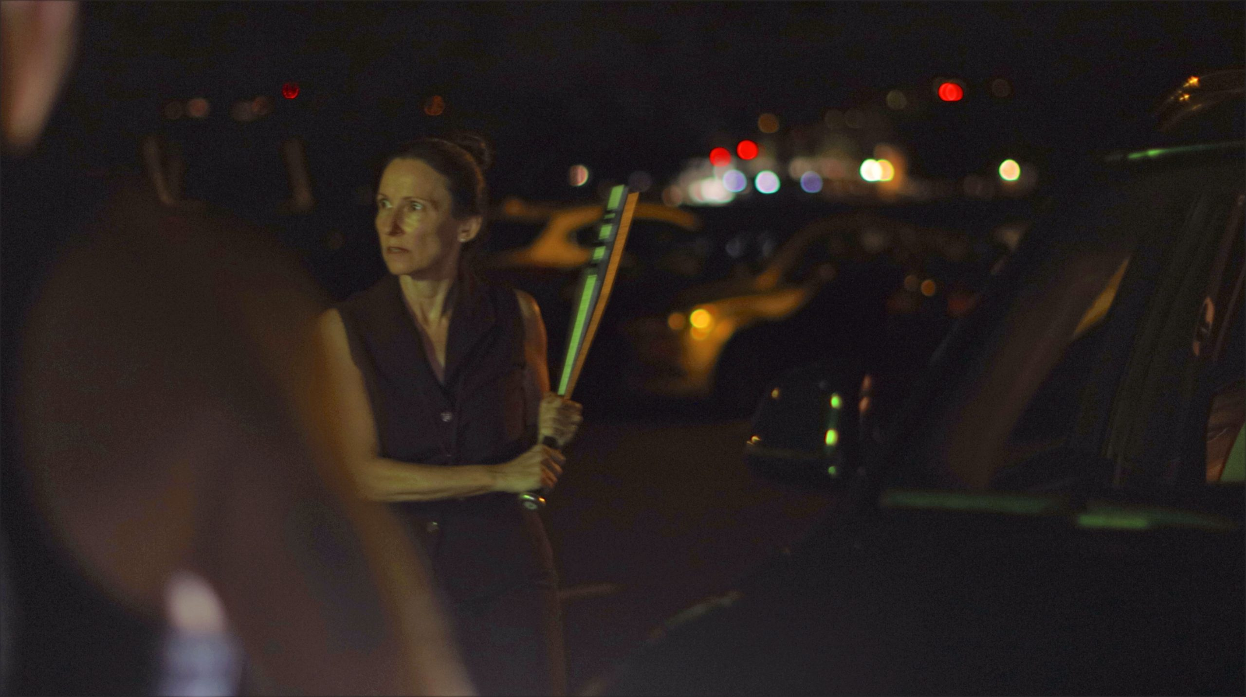 Justina Mattos as Nell holds a bat to protect Oee.