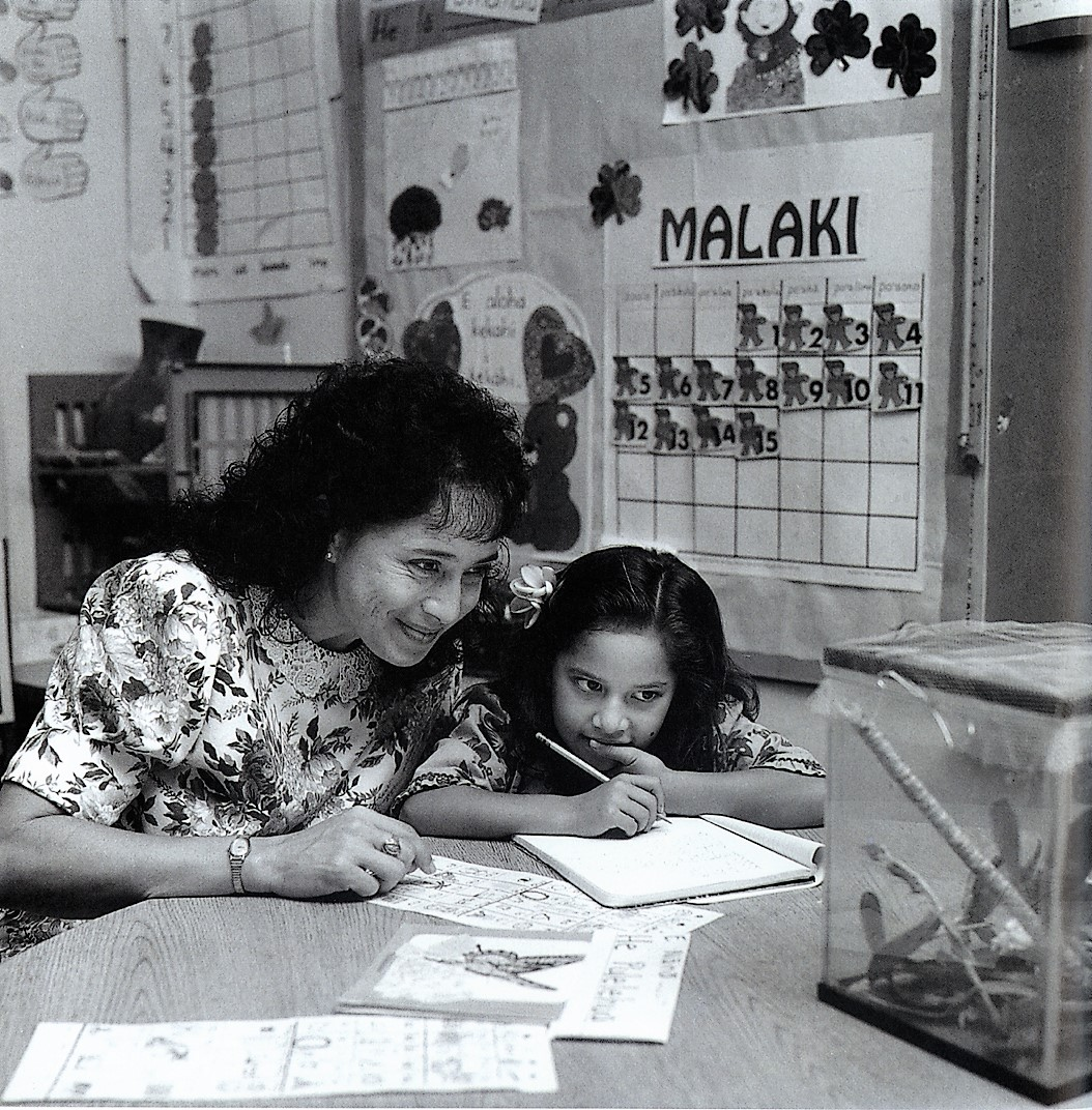 Black and white photo. Teacher and student with terrarium, student taking notes.