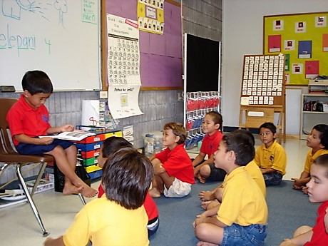 Boy sitting in chair reading to classmates who are seated on the floor.