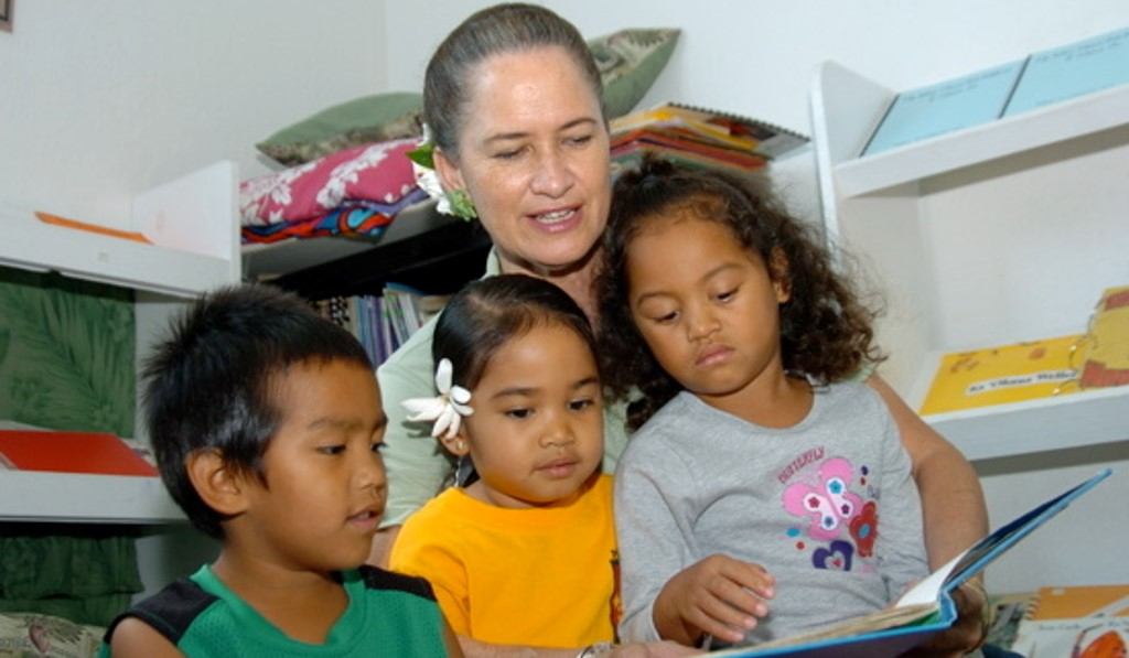Woman with three children on her lap, one holds a book.