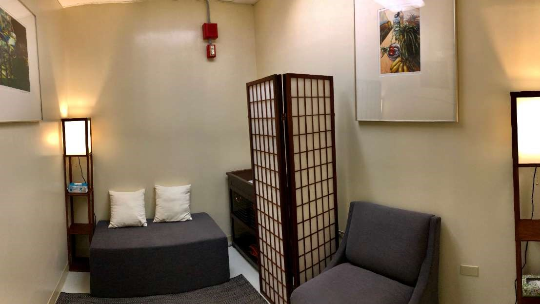 Comfortable room with wide chairs and couch, soft lighting, art on walls.
