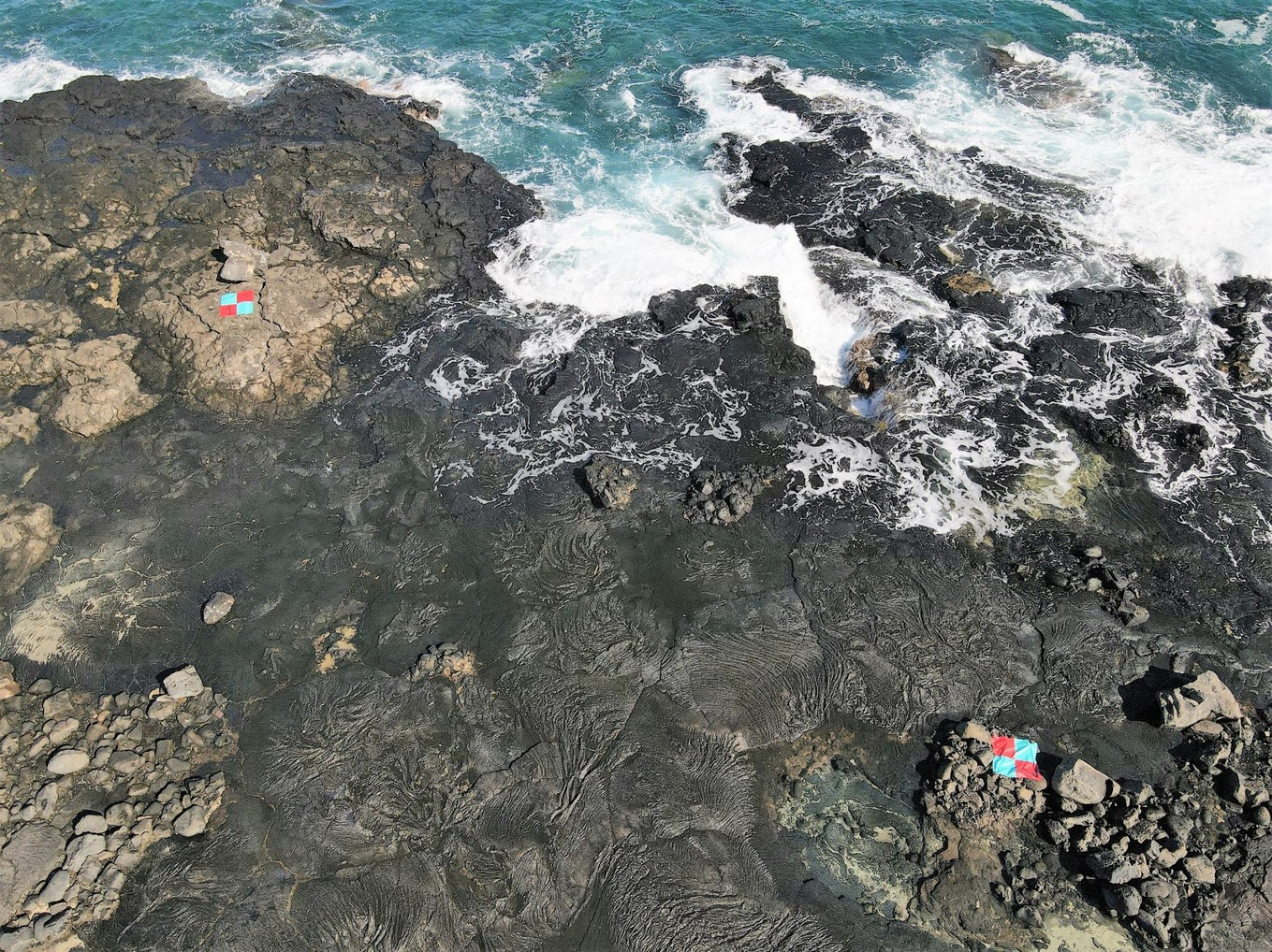 Aerial of rocky coast with two measurement markers.