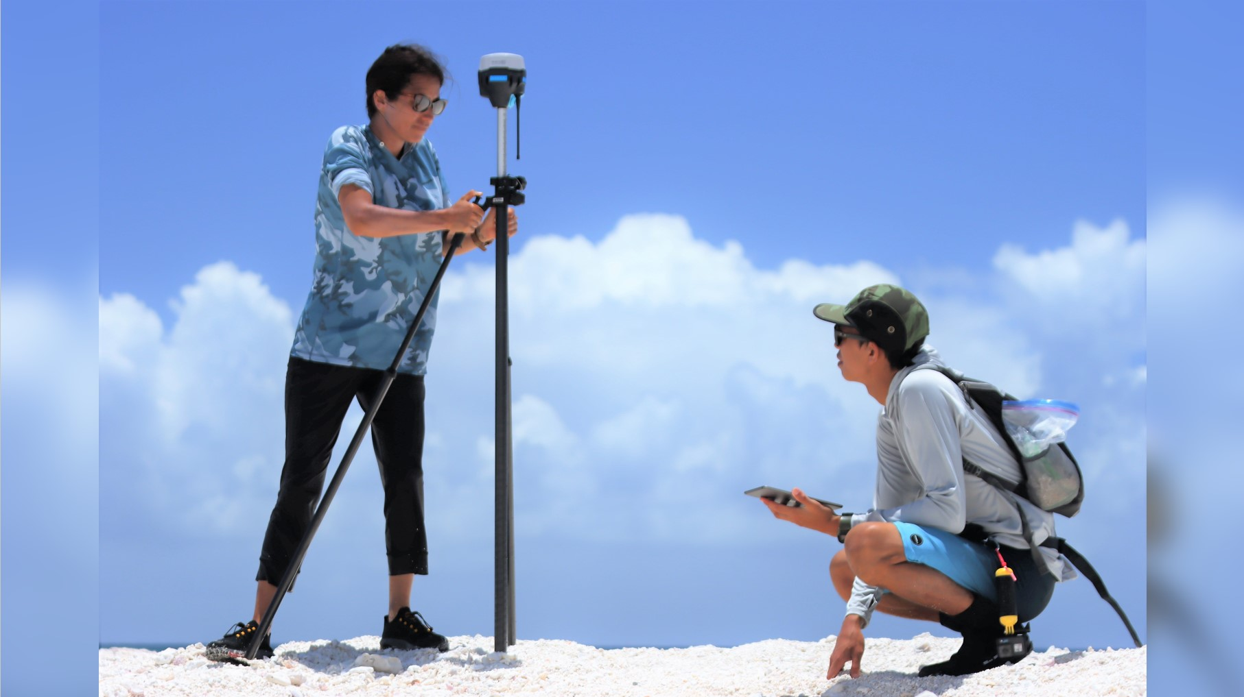 Two people on sandy area using measuring equipment.