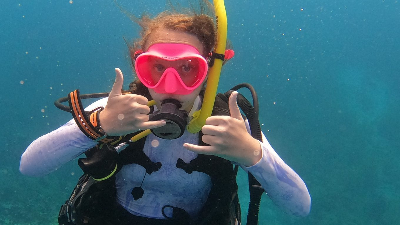 Kara Murphy is pictured underwater in SCUBA gear. She wears a pink dive mask and is doing the double shaka at the camera.