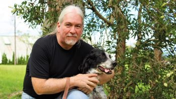 Pictured is Prof. Binder with his arm around his dog Peppers.