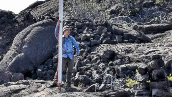 Richy Chang pictured with leveling rod on lava field outcrop.