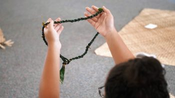 A student holds up a ti lei.
