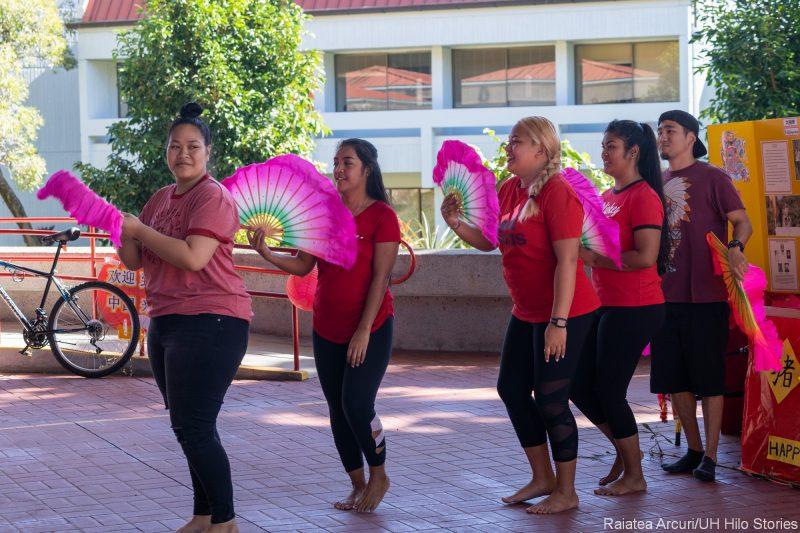 Women group doing fan dance with pink fluttery fans.