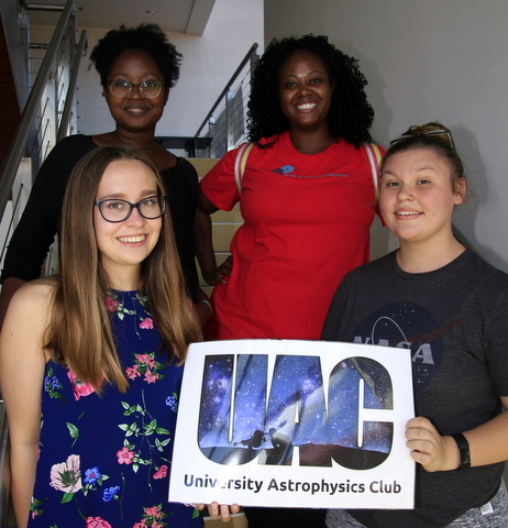 Club Officers holding up a sign that says UAC