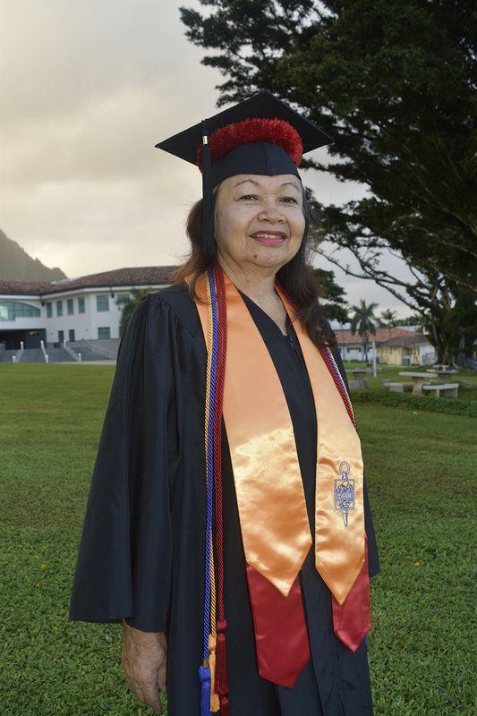 Wanda Hanson poses in commencement regalia on campus