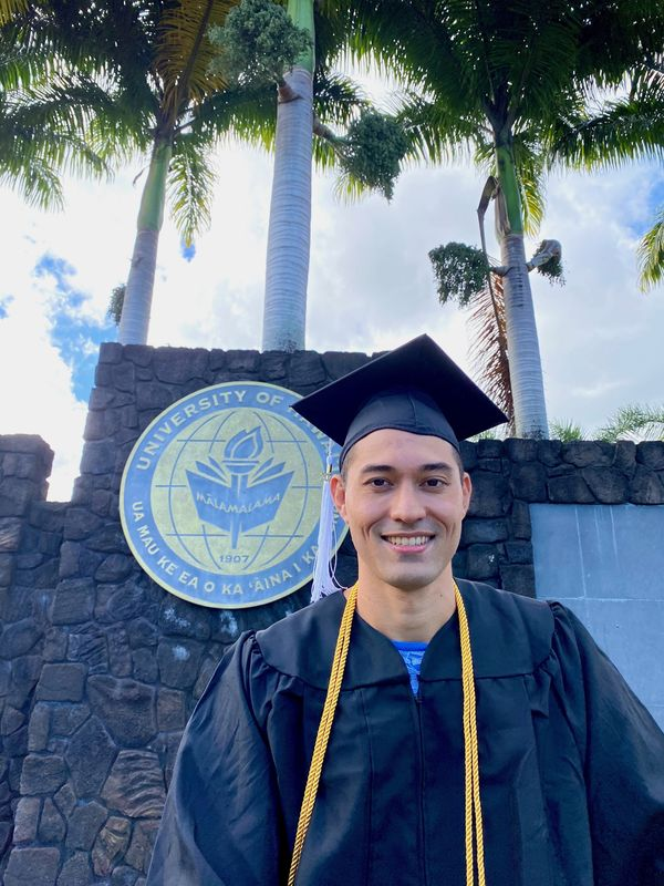 Tizan Pasang in a cap and gown next to the UH Hilo sign