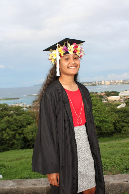 Jenaleigh Ligow wearing flowers on her graduation cap, and gown