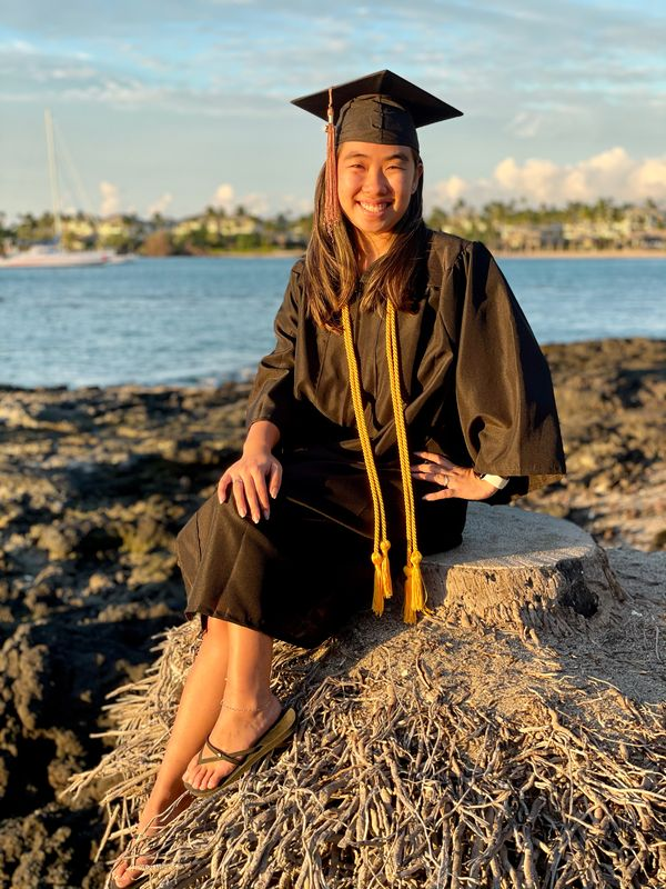 Kimberly Chiemi Kamei posing outside in her cap and gown