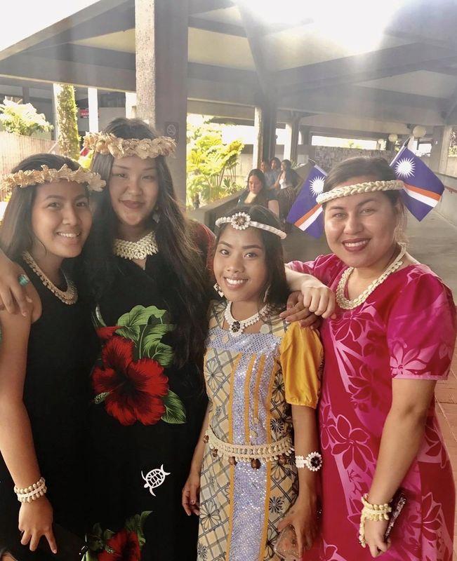 Several international students pose at the Library Lanai